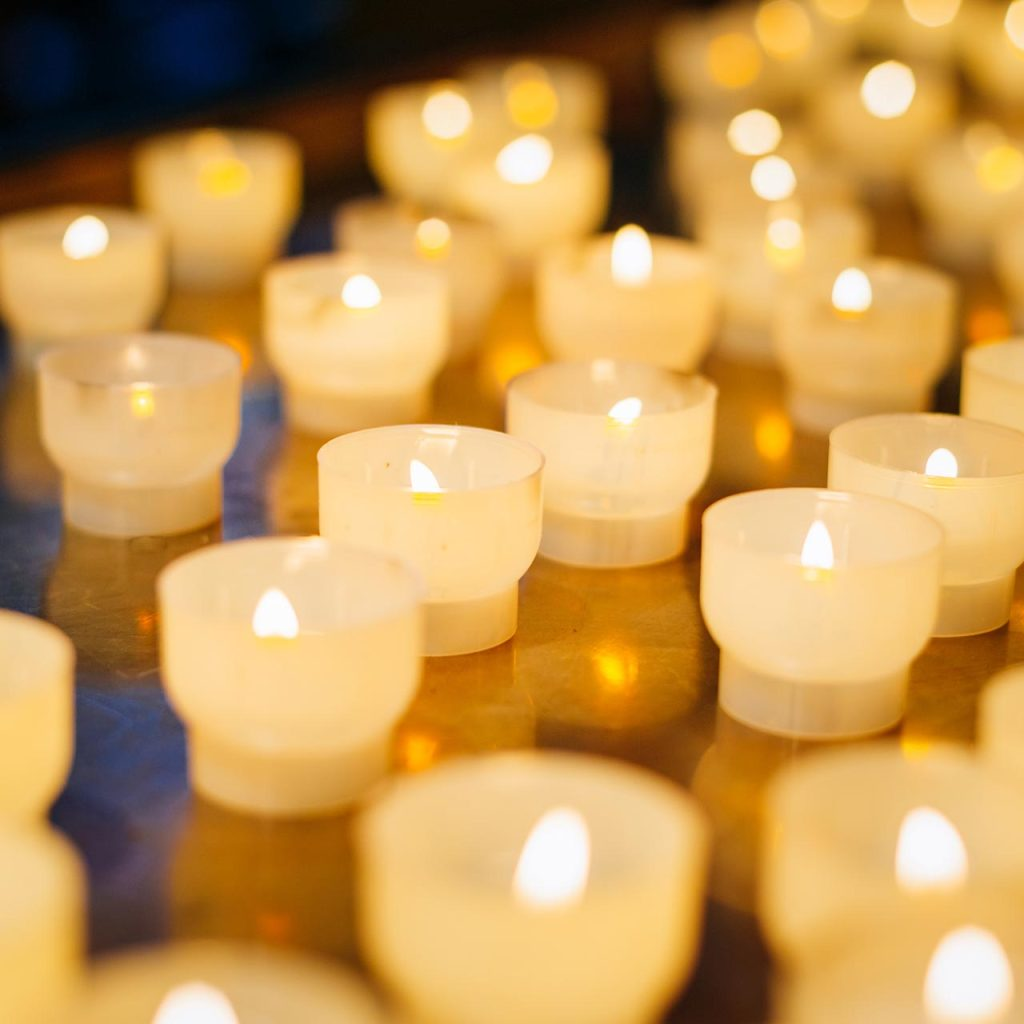 Multiple lighted votive candles with an orange glow