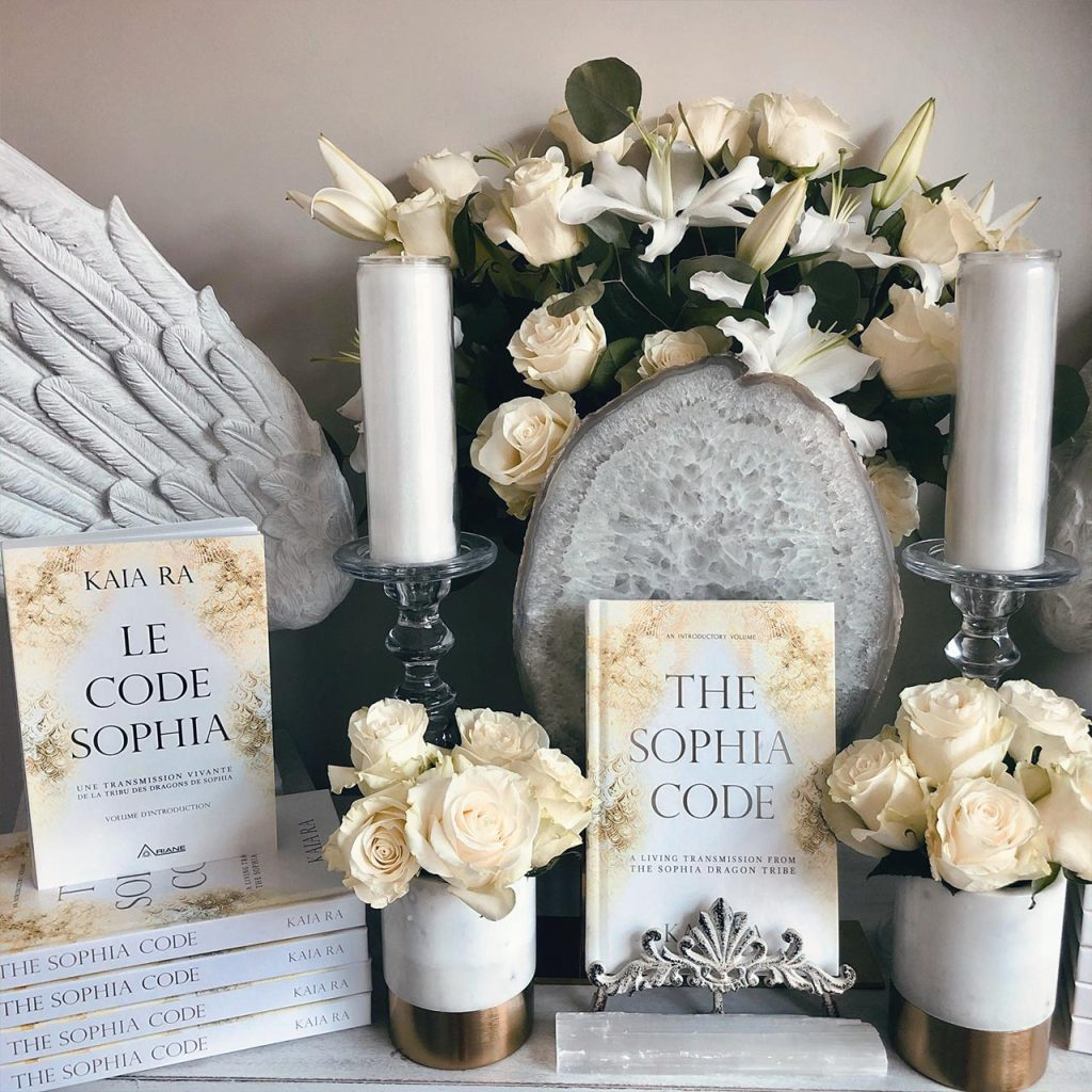 Copies of The Sophia Code book surrounded by candles and flowers