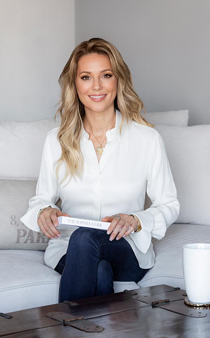 Kaia Ra in white shirt and black pants with gold pendant necklace sitting on white sofa with a copy of The Sophia Code on her lap